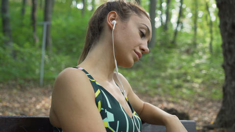 Fit girl lost in thoughts, relaxing on a bench, choosing song from phone. Girl Live Action