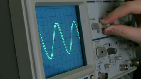 Amplitude Diagram on the oscilloscope. A man presses the buttons on the device Live Action