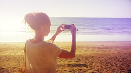 Young Woman Taking Pictures with Smartphone on Beach 이미지
