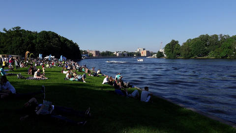 Many people in small groups sit and rest on park lawn against river Footage