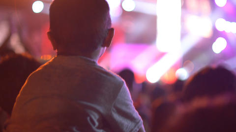 Baby sits on shoulders of Dad at concert Footage