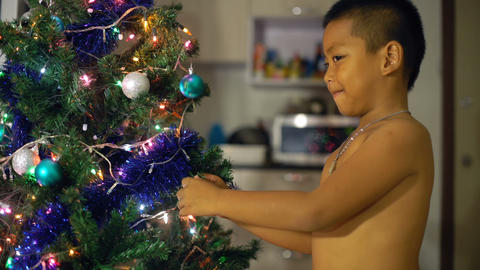 Little asian Boy decorating Christmas tree Footage