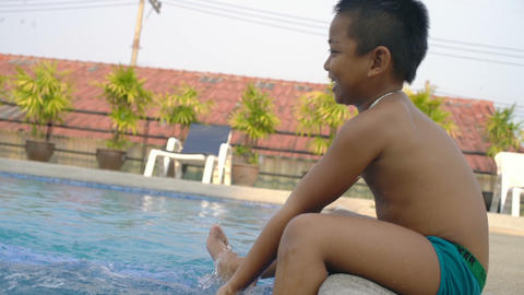 Little boy sits near swimming pool and plays with water slowmotion Footage