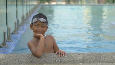 Portrait of little boy on swimming pool edge slowmotion Footage
