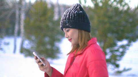 Young Woman using smartphone in winter park Footage