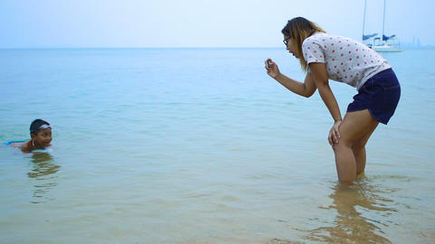Young woman takes photo her son on beach slowmotion Footage
