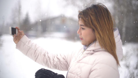 Young Woman taking selfie during snowfall. Slowmotion Footage