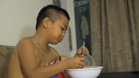 Little Thai boy eating instant noodles Footage