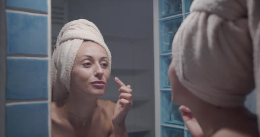 Young beautiful woman touching skin in bathroom. Morning skincare routine Footage