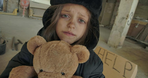 Close-up of a dirty face of a Syrian refugee holding teddy bear and asking for Live Action