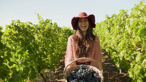 Woman with a basket of grapes in hands laughing GIF