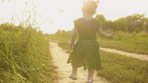 Baby girl wearing green dress walks along the path on a hot sunny summer evening Footage