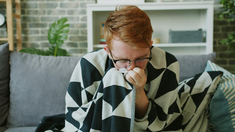 Unwell man taking paper tissue and sneezing feeling bad at home alone Live Action