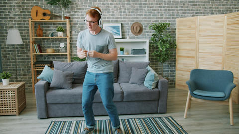 Slow motion of young man dancing in headphones singing in remote control at home Footage