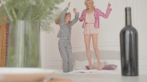 Two young blonde girls jumping on the soft bed and laughing. Cheerful friends Footage