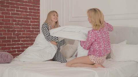 Two young cheerful Caucasian girls pulling a blanket at the bedroom. Happy Footage