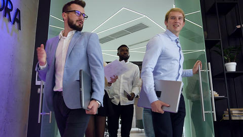 Multiracial 30s high-spirited business people entering to the modern office Live Action