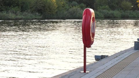 Lifebuoy at quite harbor river marina in summertime sunset or sunrise Live Action