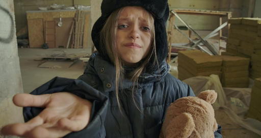 Portrait of a Syrian refugee in dirty winter clothes holding the teddy bear and Live Action