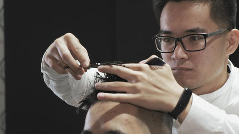 close-up of male hairdresser hands combing and cutting hair to client in salon Live Action
