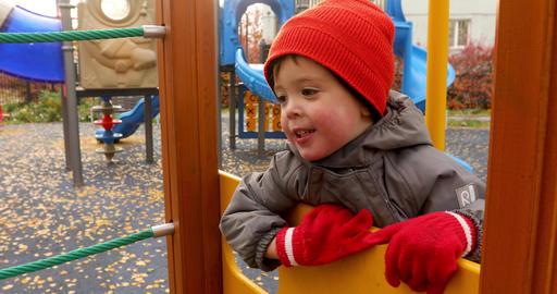 Happy preschool boy on playground in daytime Footage