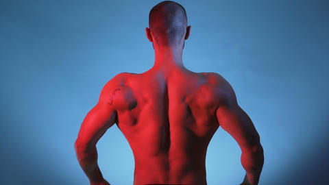 Bodybuilder Performing Rear Lat Spread Pose and posing for studio session Footage