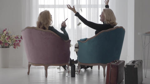 Back view of rich Caucasian ladies sitting in comfortable armchairs and throwing Live Action