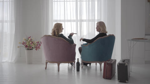 Back view of rich mature Caucasian women sitting in comfortable armchairs and Live Action