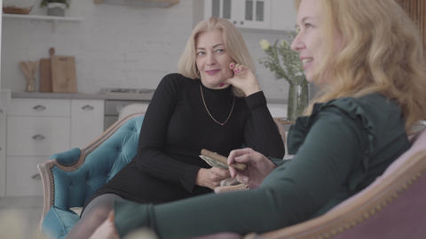 Two happy mature Caucasian women sitting in comfortable armchairs holding money Footage