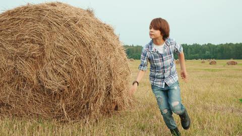 Teenager boy running on farming field on haystack background. Girl teenagers Footage