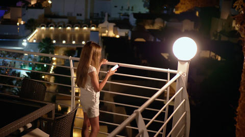 Teenager girl holding mobile phone on night balcony. Young girl using smartphone Live Action