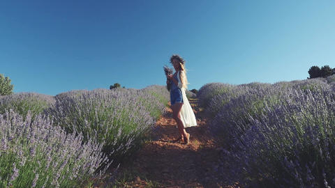 Young woman in casual clothes standing in the lavender field Live Action