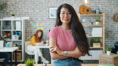 Portrait of attractive Asian lady standing indoors in office with arms crossed Footage