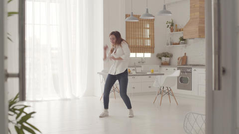 Energetic dance of a cheerful Caucasian girl in casual clothes in the light Live Action