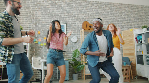 Slow motion of cheerful youth multi-ethnic team dancing in office clapping hands Footage