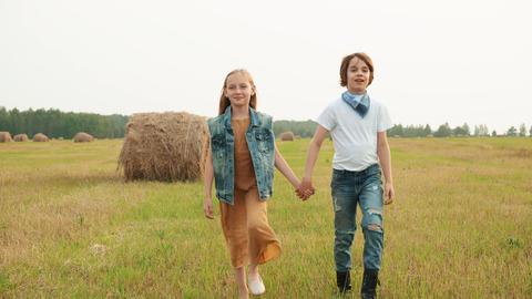 Teenager couple walking on rural field on haystack background. Happy teenagers Footage