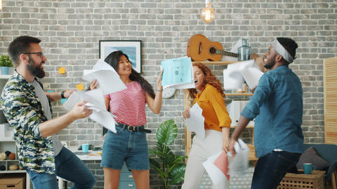 Excited employees young people dancing at office party holding business contract Live Action