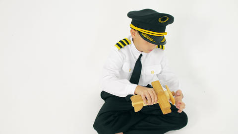 Boy wearing pilot's uniform plays with wooden plane Live Action
