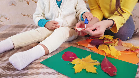 Mom and little daughter make autumn applique from autumn leaves. Little girl Live Action