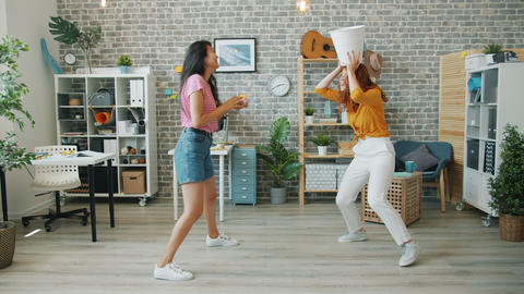 Happy young women office workers having fun at work throwing paper in bin Footage