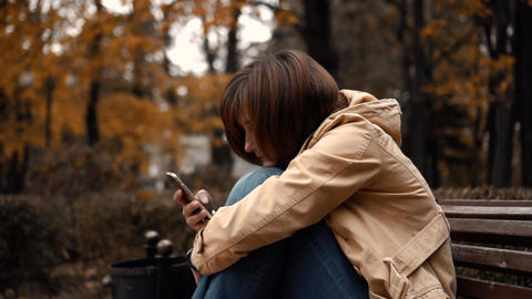young girl sitting alone in a park with a phone Live Action
