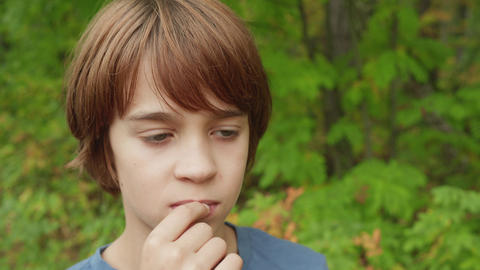 Portrait thinking teenager boy in summer park. Handsome teenager boy chewing gum Live Action