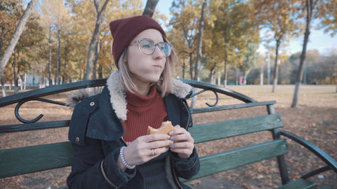 Girl on a bench in the park eating Burger. Girl in a jacket and hat Live Action