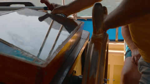 Hands of captain turning steering wheel sailing yacht. Male hands turning ship Live Action