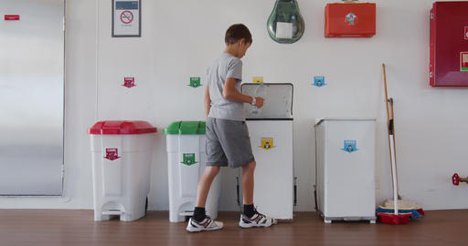Boy throws a plastic bottle into the right trash can. Recycling plastic, proper Footage
