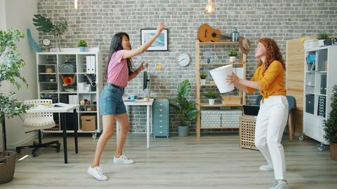 Joyful girls playing basketball in office throwing paper in bin laughing Footage