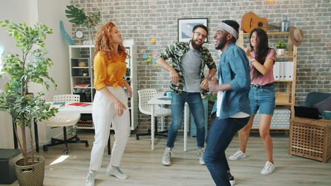 Excited young people dancing at corporate party clapping hands in modern office Live Action
