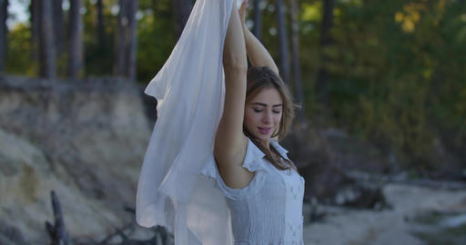 Pretty Caucasian woman standing in the forest with light white scarf blown by Footage