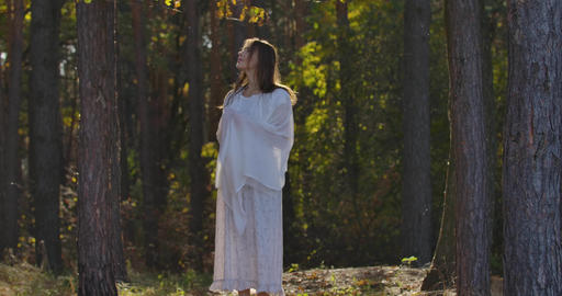 Charming Caucasian woman wrapped in light white shawl standing in sunlight in Footage