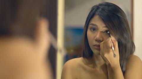 Young Woman Applying eyeliner to bottom eyelid Footage